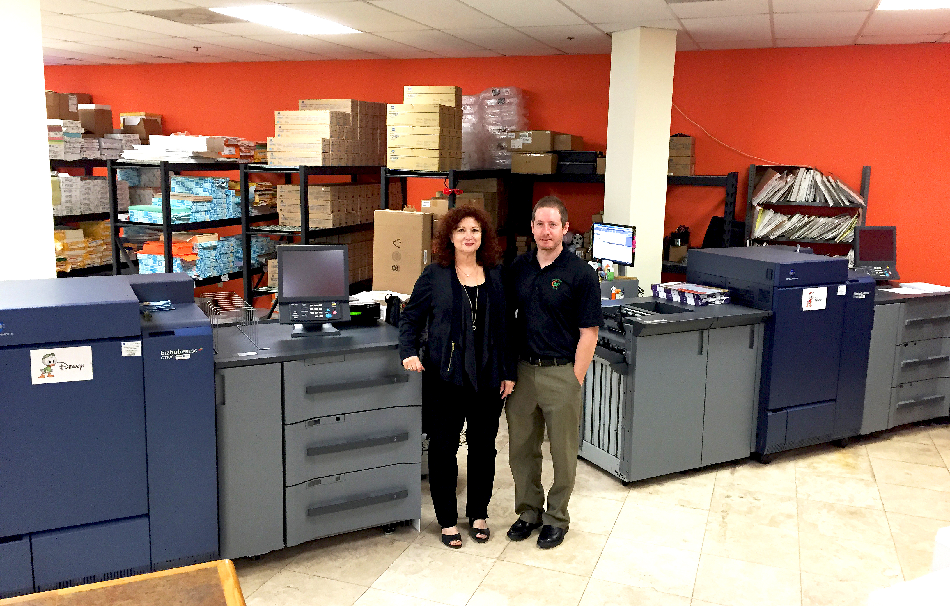 Minuteman Press franchise owner Matthew Perry (right) and his mother Gail alongside two Konica Minolta bizhub PRESS® 1100s. http://www.minutemanpressfranchise.com