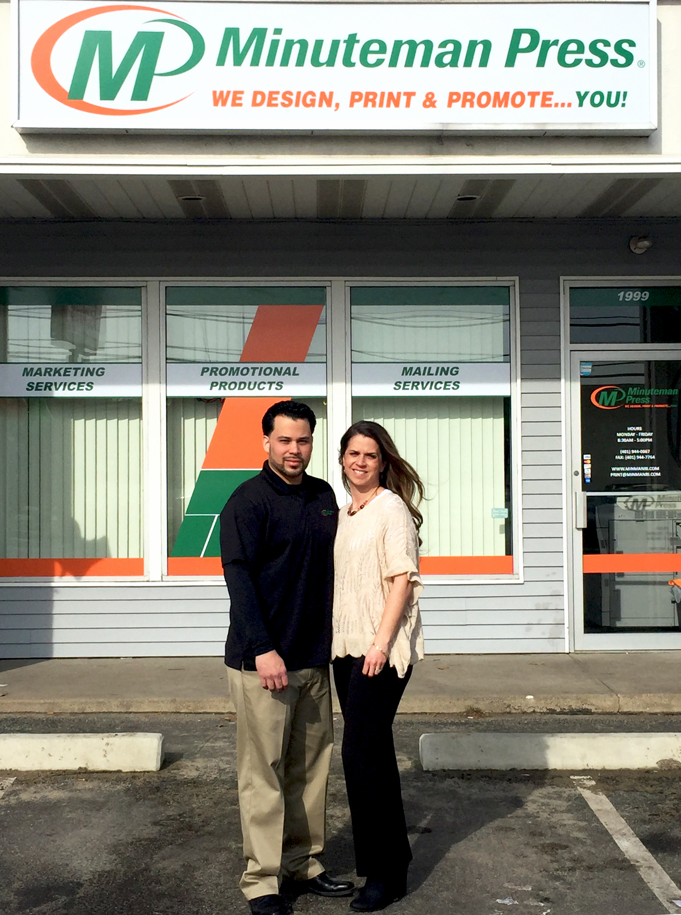 Jorge Leon and Kimberly Sherman-Leon stand in front of their Minuteman Press franchise storefront in Johnston, RI with new signage and window graphics. http://www.minutemanpressfranchise.com