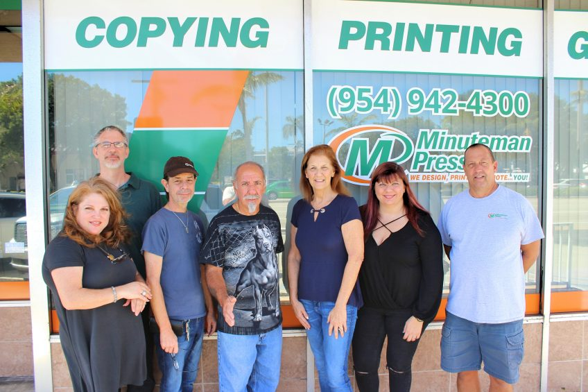 Gloria Jacaruso (center, 3rd from right) and her team at the Minuteman Press marketing and printing franchise in Pompano Beach, Florida. http://www.minutemanpressfranchise.com