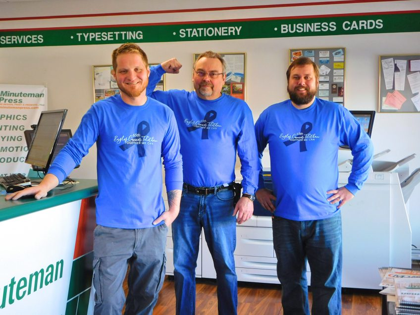 The team of Minuteman Press in Rochester, MN wears shirts for the 65th Eagles Cancer Telethon – L-R: Aaron Dahl, Apparel Technician; Dale Lipsky, Owner; and Alex Meyer, Graphic Designer. https://minutemanpressfranchise.com